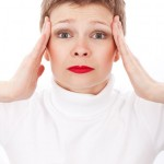 Woman with hands on head looking stressed or as if she has a headache