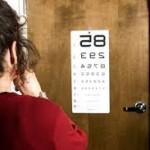 Woman getting an eye exam, looking at an eye chart