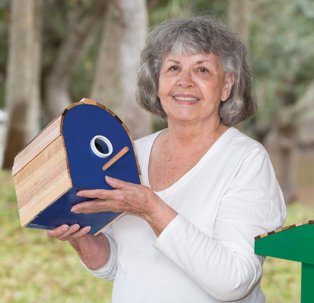 Robin Black on her patio holding a blue birdhouse and smiling.