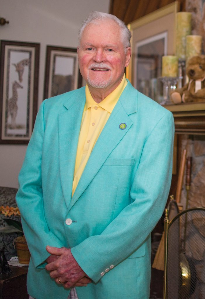 Dr. Whitney at home standing in front of his fireplace with an aqua dinner jacket on.