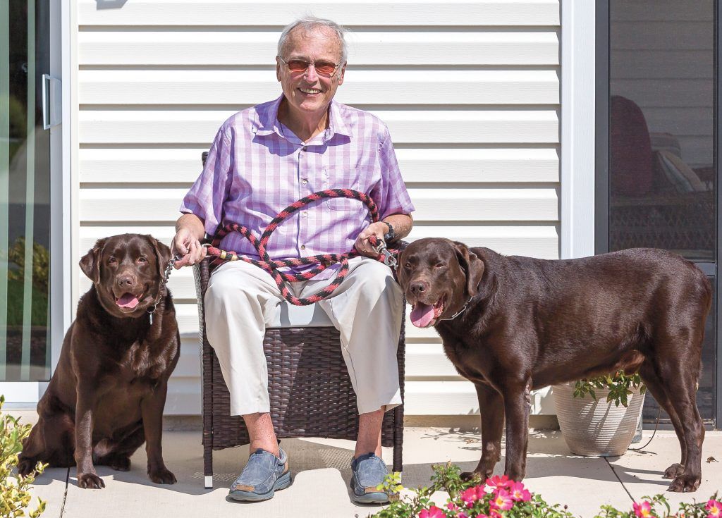 Thomas Lee sitting outsode on a deck with his two dogs.