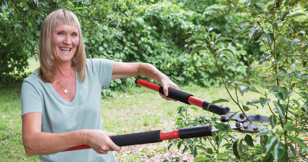 Jill Keith trimming trees in her lawn