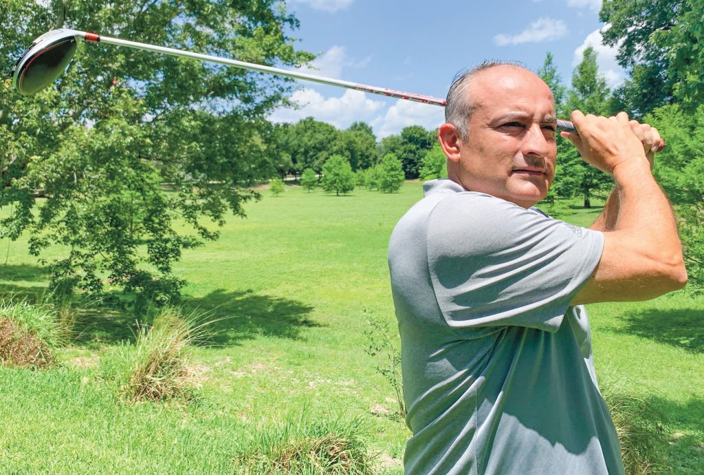 Larry Gonzalez swinging his club on the golf course