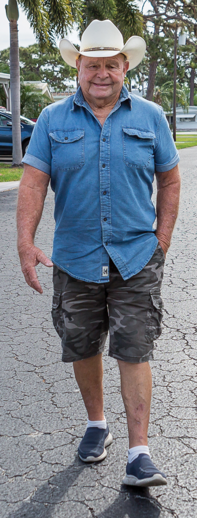 Larry Alumbaugh walking down his street with his cowboy hat on.