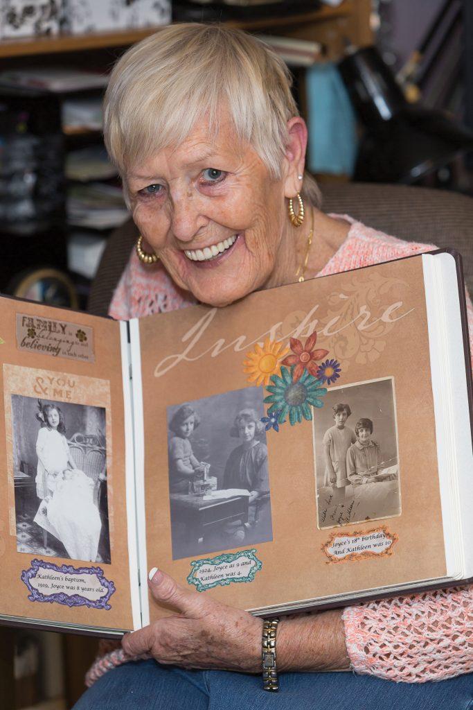 Lynda Fischer holding up a scrapbook