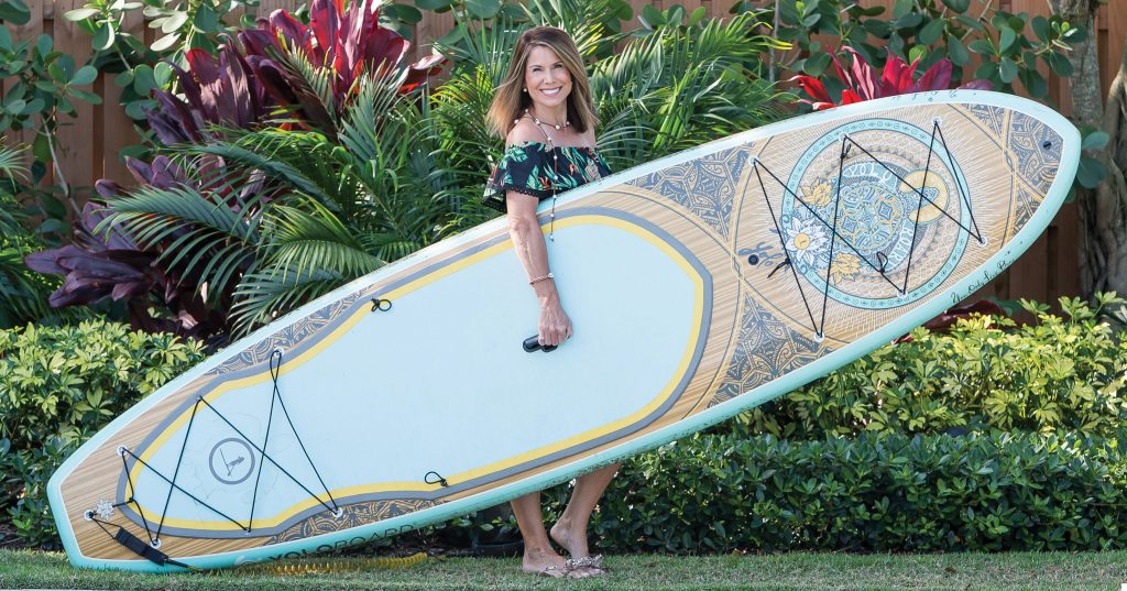 Anne Marie Rose holding a long board