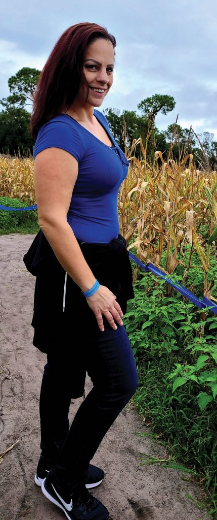 Marisa Melchiorre standing in a corn field smiling at the camera