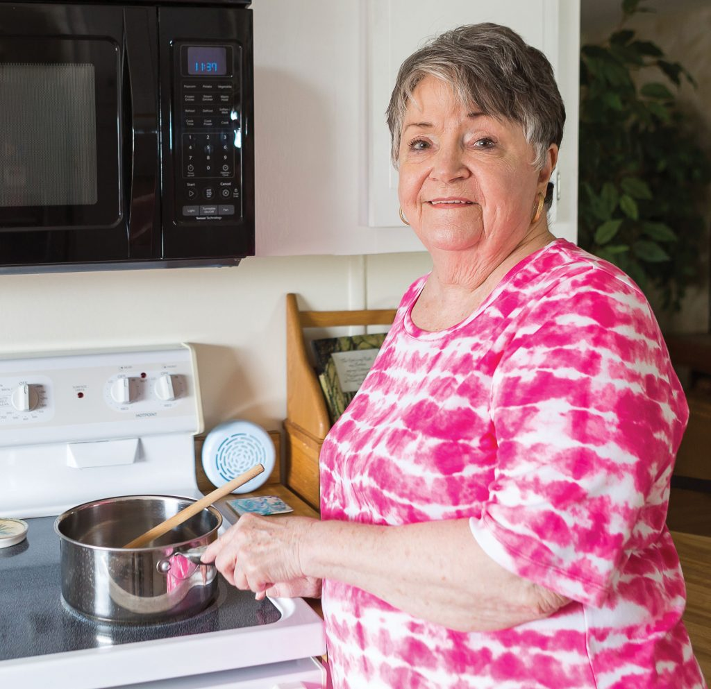 Betty Sickle in her kitchen cooking.