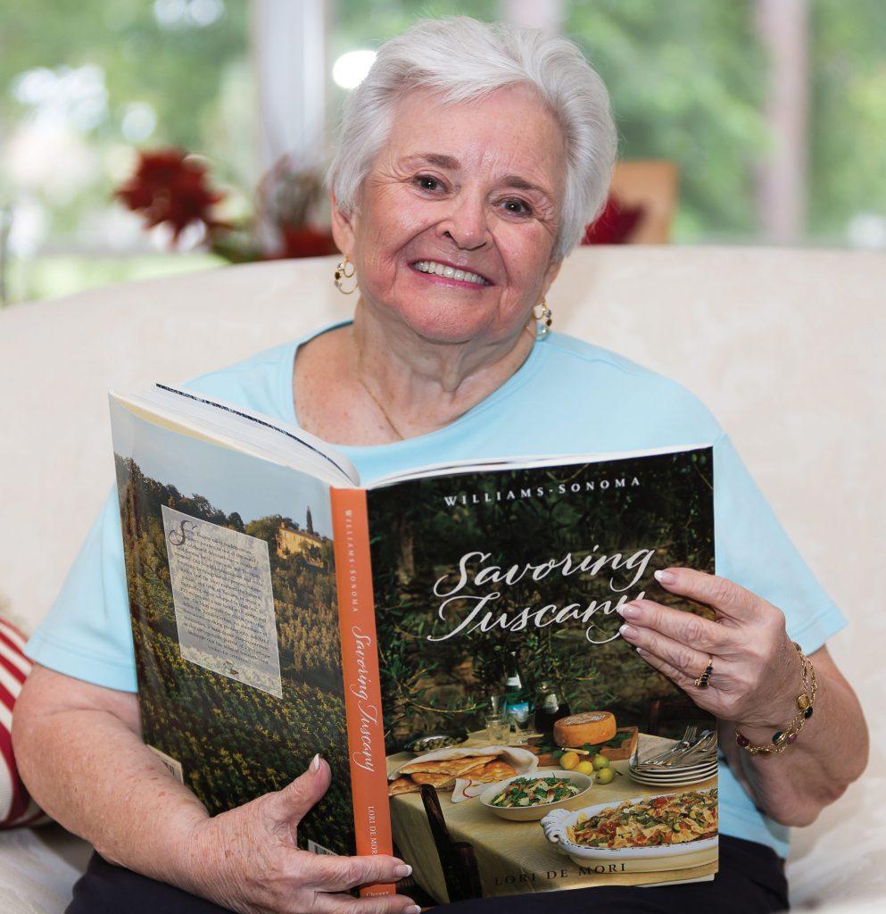 Nancy Salzbach sitting on a sofa reading a book about Tuscany