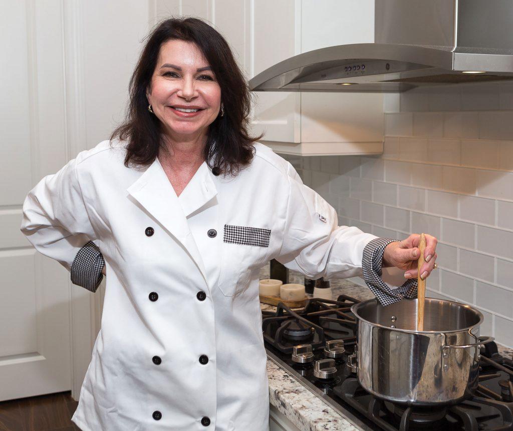 Pamela McGregor poses in her chef jacket in her kitchen.