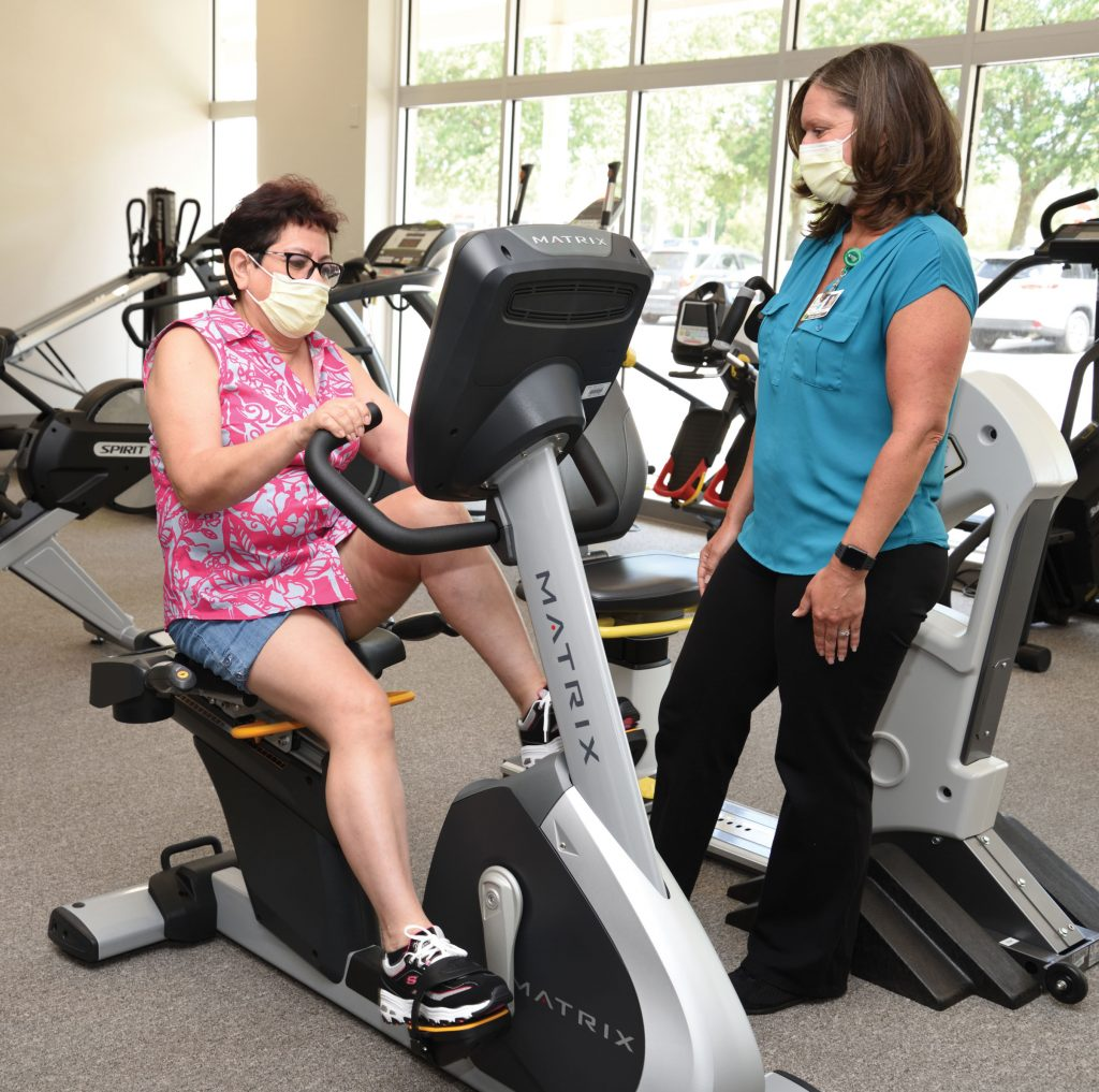Beatriz works out on machines as Monica watches.