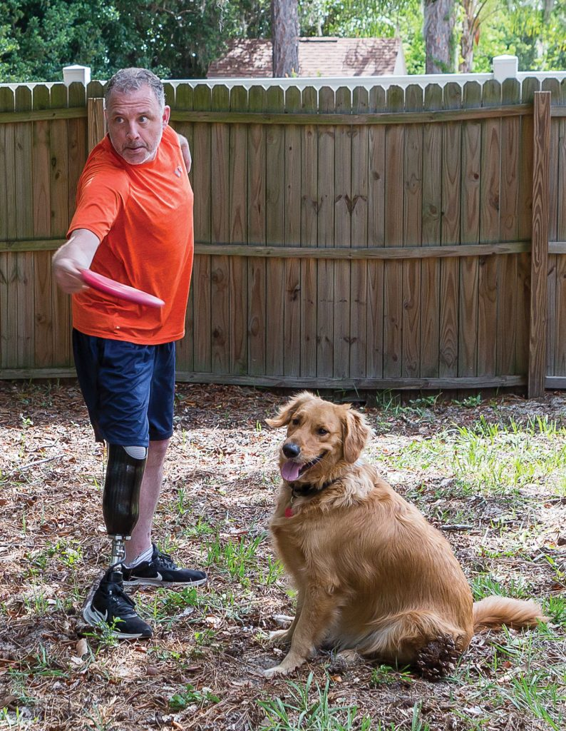 Andrew Biggart in his yard throwing a frisbee to his dog.