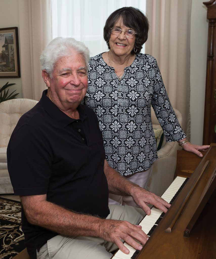 George Franzen playing the piano while his wife, Cecelia, looks on.